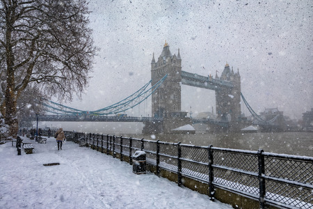 Heavy snowstorm over the Tower Bridge in London, United Kingdom; people trying to get through the snow blizzard Фото со стока