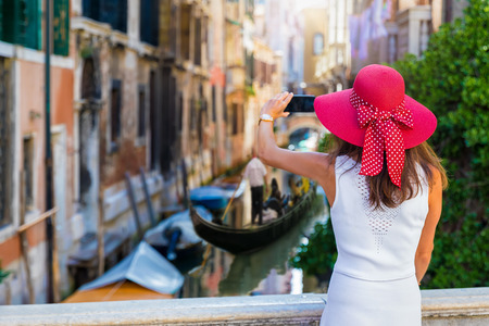 Elegant traveller woman with a red sunhat takes pictures of the little canals of Venice with Gondolas passing by, Italy