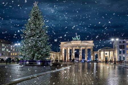 Panoramic view to the famous Brandenburg Gate in Berlin, Germany, with an illuminated Christmas tree and snow falling during a winter night