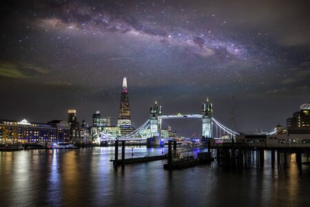 Night view to the famous Tower Bridge of London, United Kingdom, with the milky way galaxies in the sky upon it