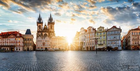 The old town square of Prague, Czech Republic, during sunrise without people surrounded by the historical, Gothic style buildings and the famous Tyn Church