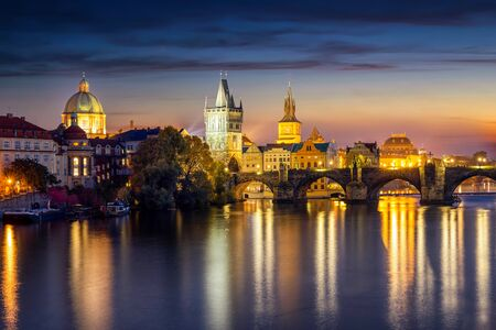 View to the illuminated Charles Bridge and Old Town of Prague, Czech Republic, during night time with reflections in the Vltava River