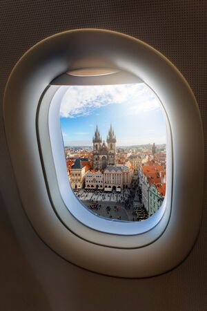 Travel concept for Prague, Czech Republic: view from an airplane window to the old town and famous Tyn Church of the European city Stock Photo
