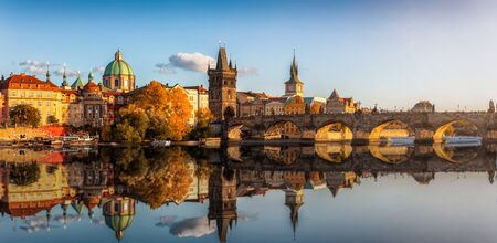 Panoramic view to the old town and Charles Bridge over the Vltava River in Prague, Czech Republic, during a golden autumn sunset time Stock Photo