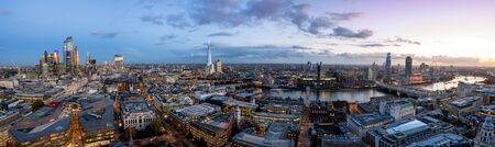 The modern skyline of London, United Kingdom, just after sunset: from the illuminated office buildings of the City along the Thames River with the famous Tower Bridge to Westminster Stock Photo