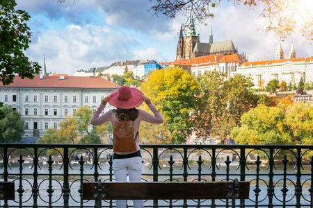 A traveler woman with red hat enjoys the view to the castle of Prague during a sunny autumn day, Czech Republic
