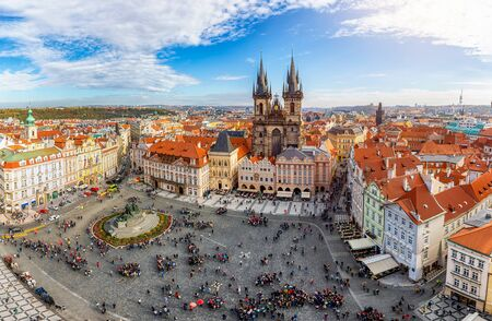 Panoramic view to the Tyn Church and with tourists crowded town square in the old city center of Prague, Czech Republic, on a sunny day