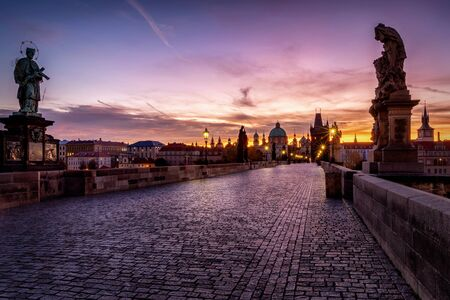 Sunrise behind the Gothic towns cape of Prague, Czech Republic, with the famous Charles Bridge leading into the old town Stock Photo