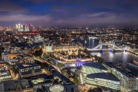 Aerial view to the illuminated skyline of London, UK, during night time featuring the famous Tower Bridge and the modern office buildings around
