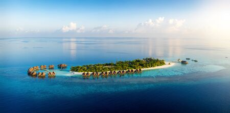 Panoramic aerial view to a tropical paradise island in the Maldives, Indian Ocean, during sunset time