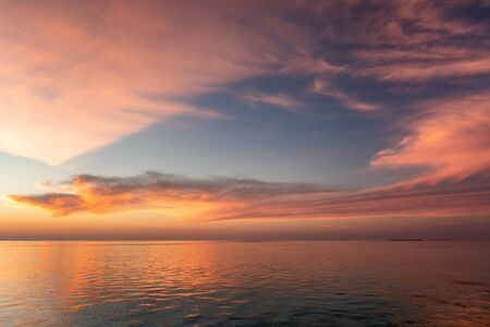 A colorful tropical sunset sky with soft blue, red and oranges tones over the sea