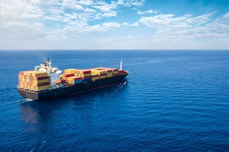 Concept of global trade and shipping industry: aerial view of a container cargo ship traveling on the open sea Stock Photo