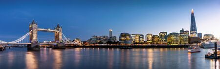 Wide panoramic view to the urban skyline of London with the illuminated, modern office buildings along the Thames river, UK
