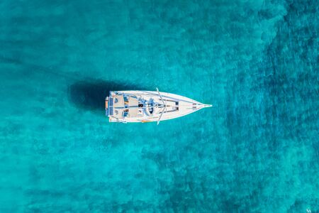 Aerial view of a white sailing boat anchored over turquoise, Mediterranean sea in Greece Stock Photo
