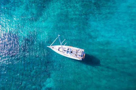 Aerial top down view of a sailing boat moored over turquoise water in the Aegean Sea, Greece 스톡 콘텐츠
