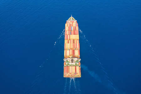 Aerial top down view to a cargo ship loaded with containers over blue ocean water