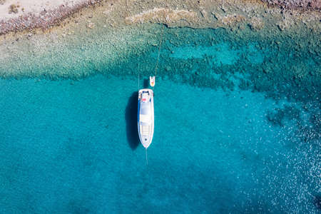 Aerial, top down view to a luxury motor yacht anchored over turquoise water as seen in the Aegean Sea, Greece 스톡 콘텐츠