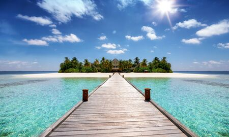 A wooden pier leading to a tropical paradise island with coconut palm trees, turquoise sea and sandy beaches