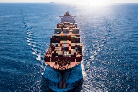 Aerial front view of a heavy loaded container cargo ship in full motion on open sea against sunlight