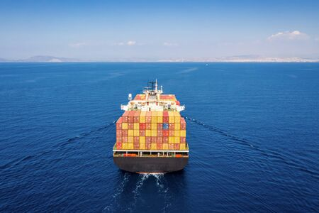 Aerial back view of a large container cargo vessel in motion approaching the main land and harbor Stock Photo