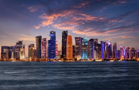 The illuminated, urban skyline of Doha, Qatar, with the modern skyscrapers just after sunset