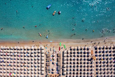 Aerial top down view to a busy beach with umbrellas very close to each other and people having fun with water sports in the turquoise sea, Greece