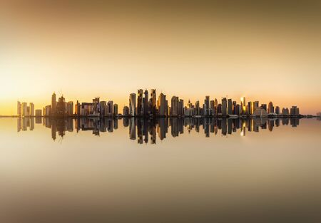The modern skyline of Doha, Qatar, during sunset time with reflections of the buildings in the sea