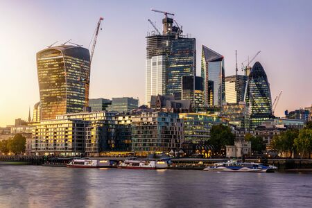 The City of London, financial district of the Metropole, just after sunset with illuminated buildings, United Kingdom