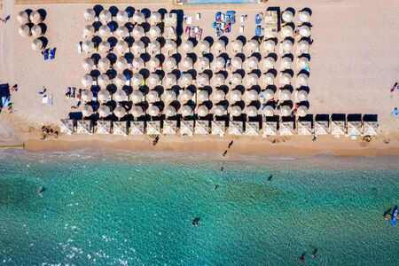 Aerial top down view to a beach with umbrellas, fine sand and emerald sea with people having fun as seen on the south coast of Athens, Greece Stock Photo