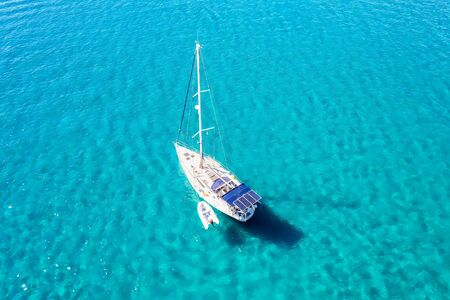 A white sailing yacht over blue sparkling, tropical sea water