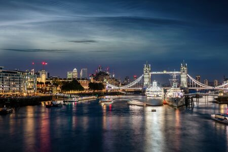 View to the skyline of London, UK, during night time over the Thames river to the Tower Bridge and Canary Wharf district Stock Photo