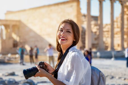 Portrait of a pretty tourist woman with a photo camera in her hand in front of the Acropolis of Athens, Greece, during a city sightseeing trip