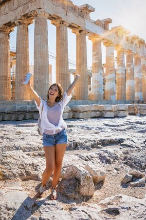 Happy female traveler woman takes selfie pictures with her mobile phone in front of the Parthenon Temple at the Acropolis of Athens, Greece