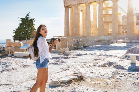 A attractive tourist woman with a photo camera in her hand explores the Parthenon Temple at the Acropolis of Athens, Greece, during her summer vacation time Stock Photo