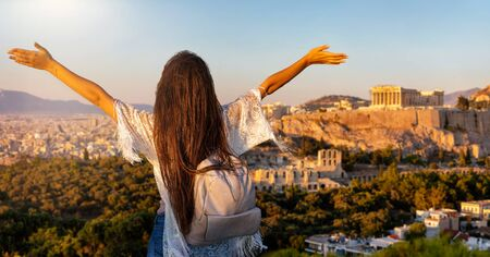 A happy female tourist woman with outstretched arms enjoys the view to the cityscape of Athens, Greece, with Acropolis and Parthenon Temple during sunset time