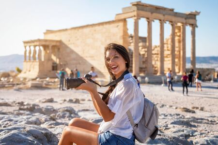 A beautiful city tourist woman with a camera in her hand explores the ancient Parthenon temple of the Acropolis of Athens, Greece Stock Photo