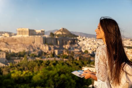A pretty female traveler woman enjoys the view to the Parthenon Temple at the Acropolis of Athens, Greece, during her summer vacation Stock Photo