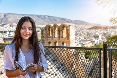 A pretty tourist woman with a travel guide on her hand stands in front of the ancient Irodion theater at the Acropolis of Athens, Greece, during her sightseeing trip in summer