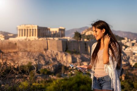 A beautiful Europe traveler woman stands in front of the Acropolis of Athens, Greece, and reads a travel guide book