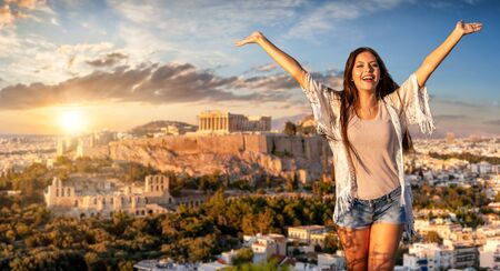 Greece traveling concept: a happy tourist woman with outstretched arms stands in front of the Acropolis of Athens Stock Photo