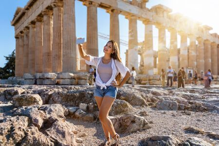 A pretty tourist woman in summer clothing takes selfie photos with her mobile phone in front of the Parthenon Temple at the Acropolis of Athens, Greece