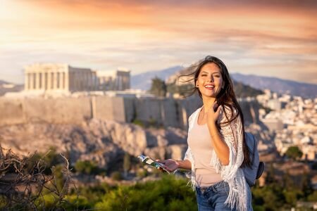 A pretty tourist traveler woman with a travel guide in her hand stands in front of the Acropolis of Athens, Greece, during sunset time Stock Photo