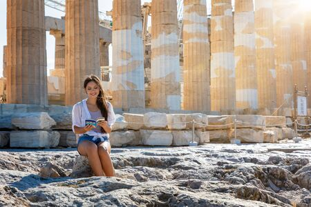 Attractive tourist woman sits in front of the columns of the Parthenon Temple at the Acropolis of Athens during summer time and reads a travel guide 스톡 콘텐츠