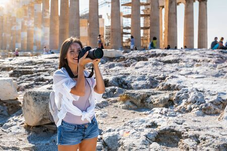 A beautiful Greece traveler woman takes photos of the Parthenon Temple at the Acropolis of Athens during a sightseeing trip