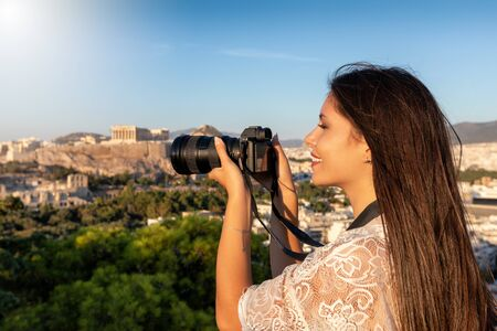 A female Europe traveler takes photographs of the cityscape and Acropolis of Athens, Greece, during her summer city vacation