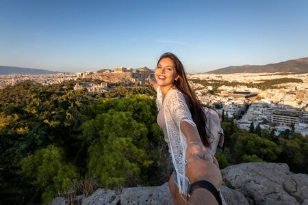 A beautiful traveler woman pulls her friend from the hand to the Acropolis of Athens, Greece, during their vacation time 스톡 콘텐츠