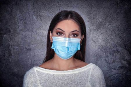 Girl in medical facemask. Masked woman looks at camera,  concept for flu, virus, respiratory disease, quarantine. Beautiful caucasian young woman with disposable face mask 스톡 콘텐츠