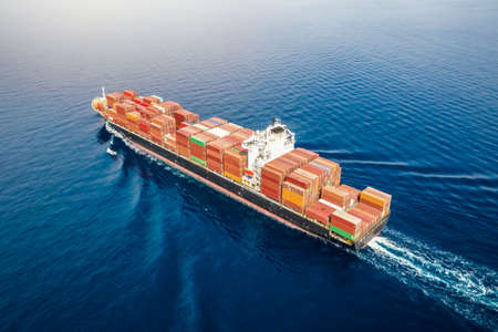 Aerial view of a big, heavy loaded container cargo ship traveling with speed over blue sea 스톡 콘텐츠