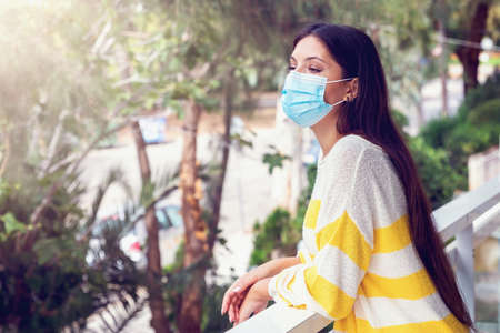 A young woman wearing a face mask stands on the balcony and looks on the street during her self isolation due to Covid-19 disease
