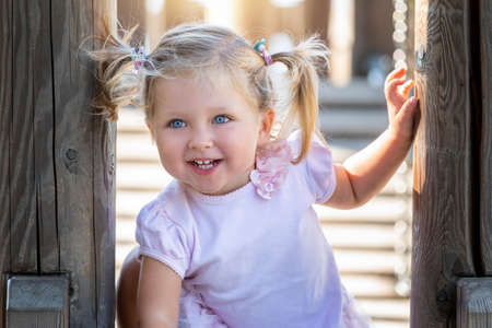 Portrait of a blonde and blue eyed baby girl with pig tails hair having fun on a playground in soft sunlight